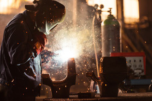 Schutzgas Schweißgerät Test - Mann schweißt in einer Werkstatt.